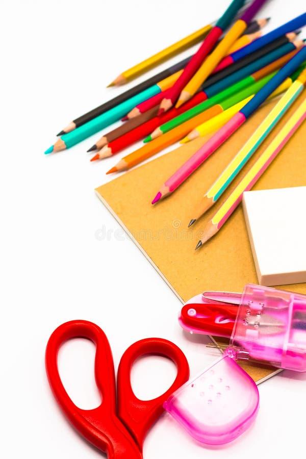 Книги, ручка, карандаш, ножницы и конторские машины на белизне стоковые фотографии rf
