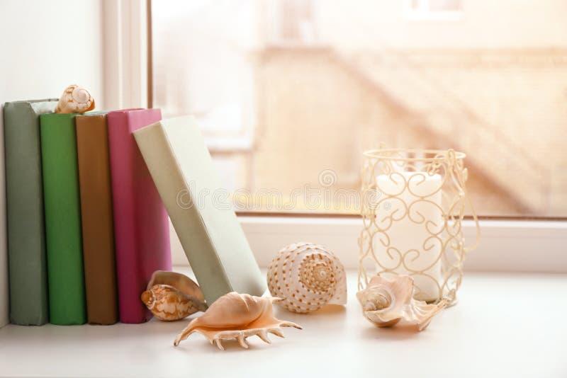 Книги, свеча и seashells на windowsill стоковое изображение