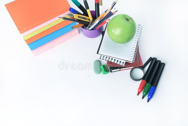 Книги, тетради и школьные принадлежности на белой предпосылке яблоко записывает красный цвет образования принципиальной схемы стоковая фотография