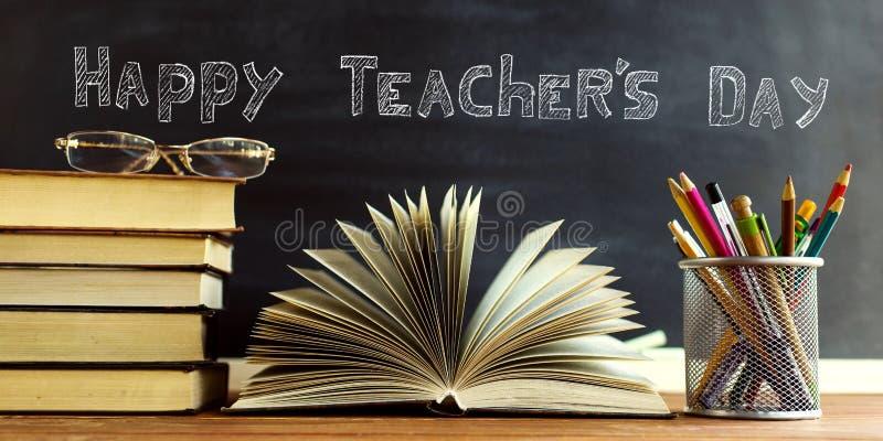 Книги учителя стекел и стойка с карандашами на таблице, на предпосылке классн классного с мелом Концепция  стоковая фотография rf