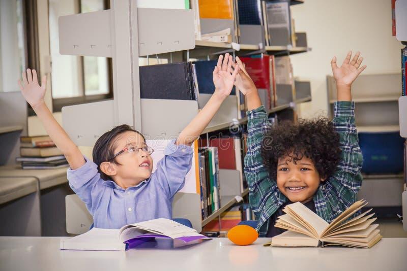 2 книги чтения маленьких ребеят на школьной библиотеке стоковая фотография