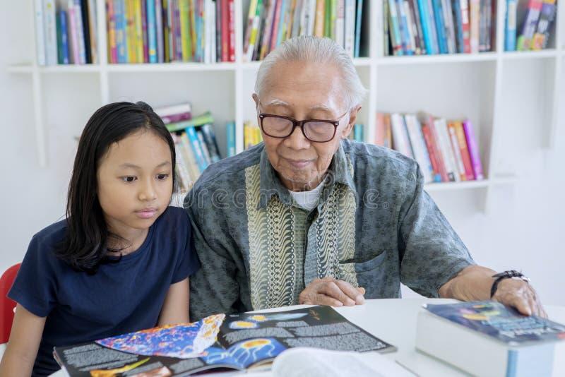 Книги чтения маленькой девочки с ее дедом стоковое фото