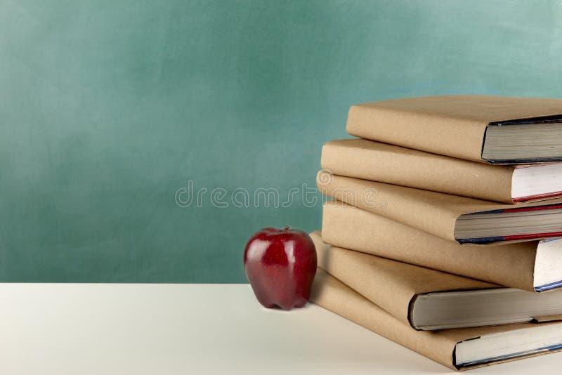 Книги, яблоко и классн классный школы стоковое фото rf