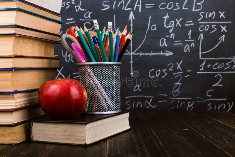 Книги, яблоко, стойка для ручек на деревянном столе, на фоне доски мела с формулами Концепция дня учителя и стоковое изображение