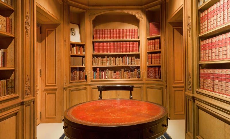 Книжные полки с старыми томами книг и античного круглого стола внутри библиотеки стоковая фотография