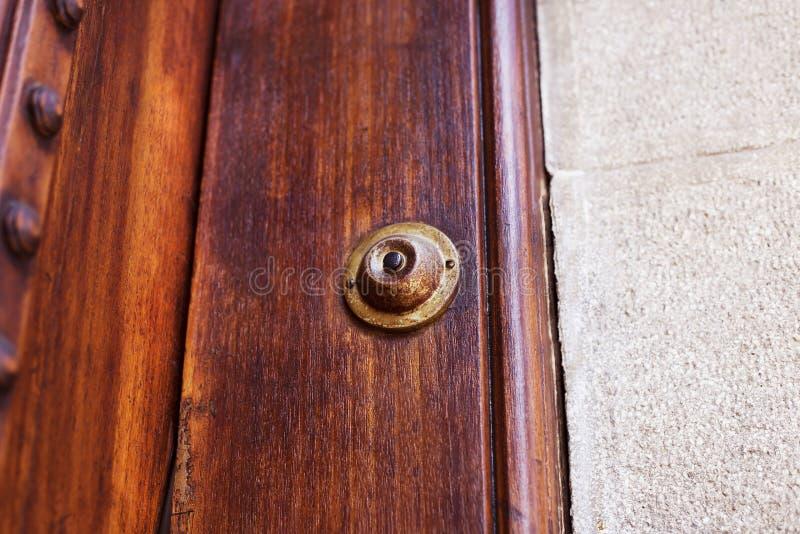 Кнопка дверного звонока старого металла винтажная на деревянной двери стоковое фото rf