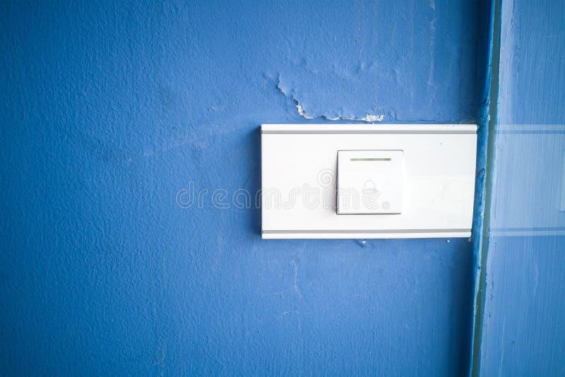 Кнопка переключателя колокола на голубой стене , предпосылка стоковая фотография rf