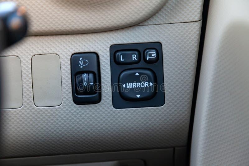 Кнопки для контролировать электрический привод зеркал на стильной панели покрытой с пефорированной справедливой кожей внутри авто стоковые фото