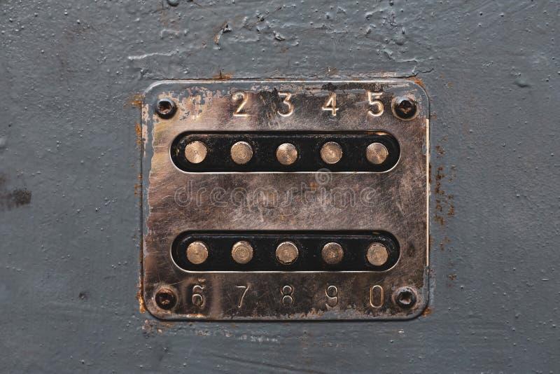 Кнопки номера медного цвета для того чтобы открыть замок Cupreous панель с номерами на старой двери металла Кнопки Unlocker на ме стоковая фотография rf