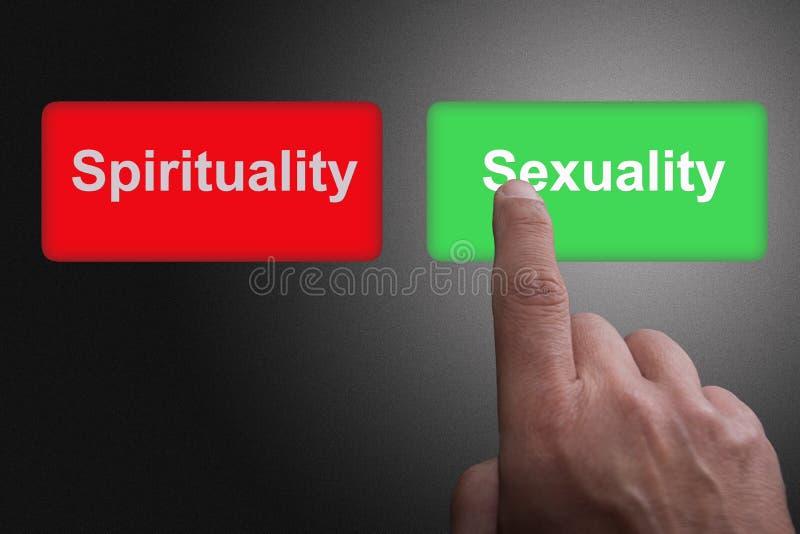 Кнопки с написанными духовностью и сексуальностью и пальцем указывать, на серой предпосылке градиента стоковое фото