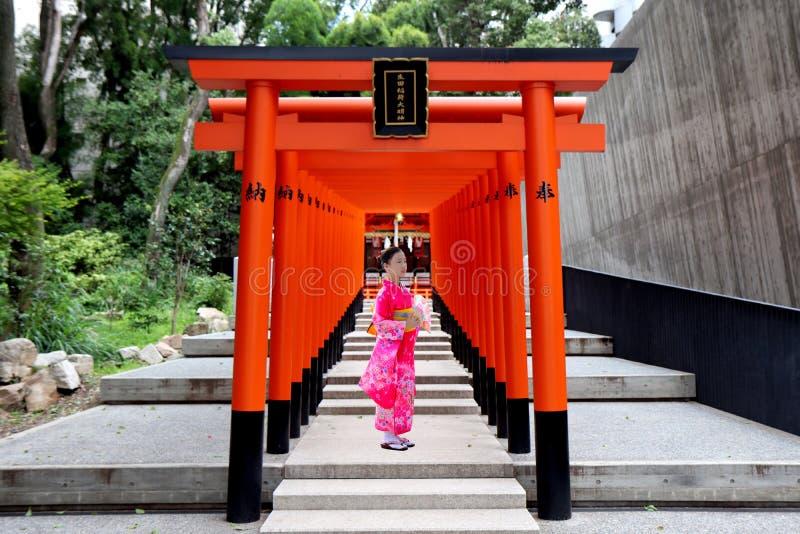Кобе, Япония, 15-ое июля 2019, розовый девочка-подросток кимоно стоит в Torii аранжировало параллель к святыне Ikuta стоковые фото