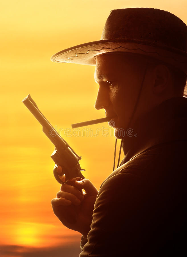 Ковбой в шлеме с сигарой и револьвером стоковые фотографии rf