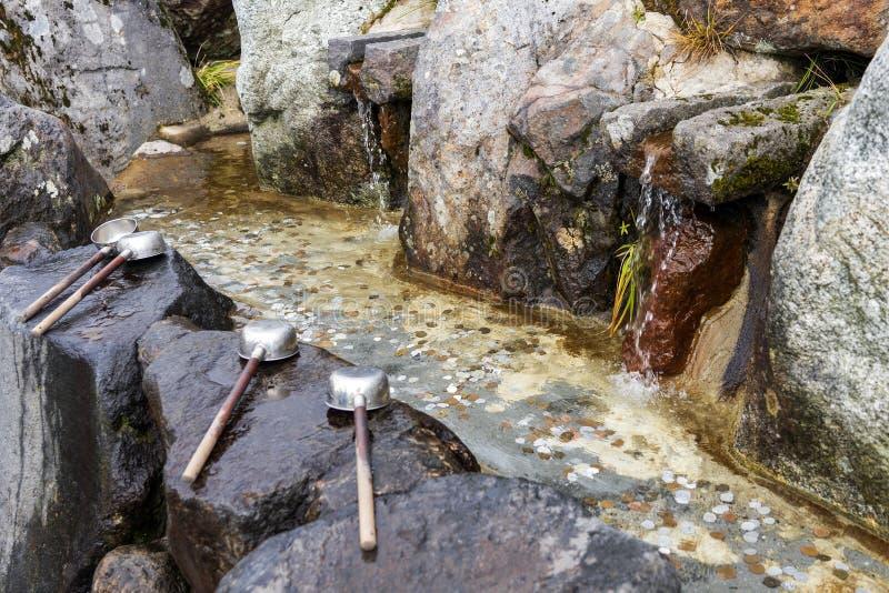 Ковши и пруд воды полный монеток стоковая фотография