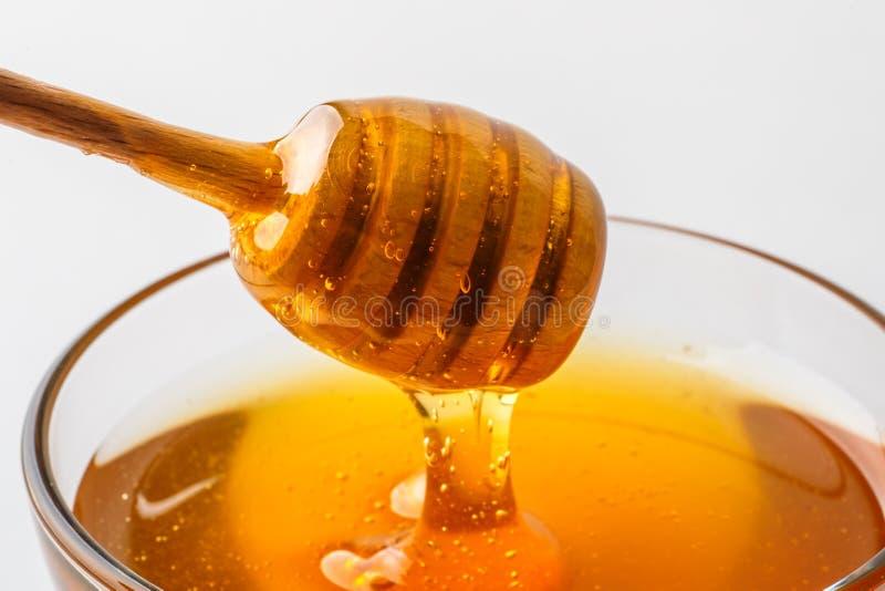 Ковш меда с стеклянным шаром на белом конце-вверх предпосылки, здоровым органическим натуральным продучтом стоковое изображение