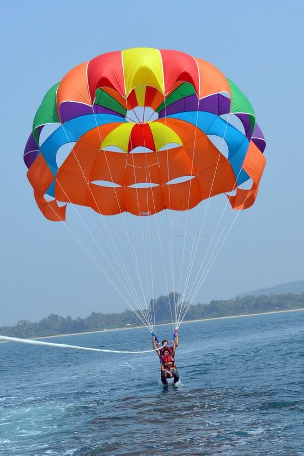 Когда люди летают в голубом небе, используя красочный парашют стоковое изображение rf