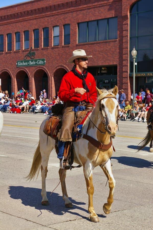 Коди, Вайоминг, США - ковбой с ярким красным катанием рубашки на параде Дня независимости стоковые изображения