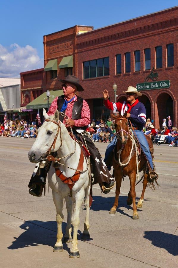 Коди, Вайоминг, США - 4-ое июля 2009 - 2 всадника приветствует зрителей пока едущ с парадом Дня независимости стоковые изображения rf