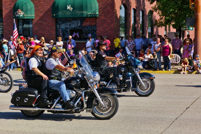 Коди, Вайоминг, США - 4-ое июля 2009 - человек и женщина ехать мотоцикл совместно в параде Дня независимости стоковое изображение