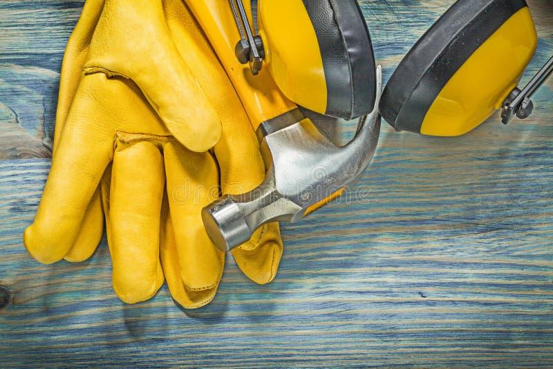 Кожаное желтое ухо перчаток безопасности muffs молоток с раздвоенным хвостом на деревянной горжетке стоковая фотография rf