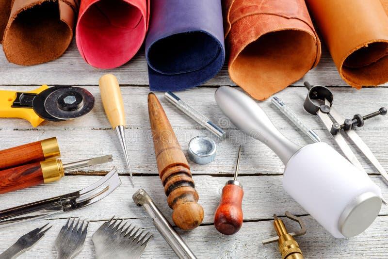 Кожаные инструменты и утвари ремесла на деревянной предпосылке стоковое фото rf