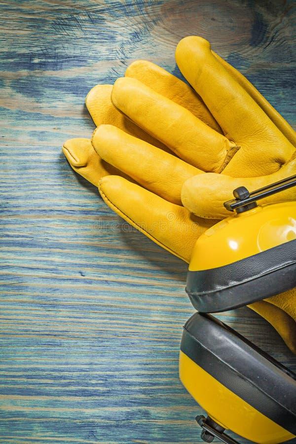 Кожаные перчатки безопасности шумят халявы уха изоляции на деревянной доске стоковые фотографии rf