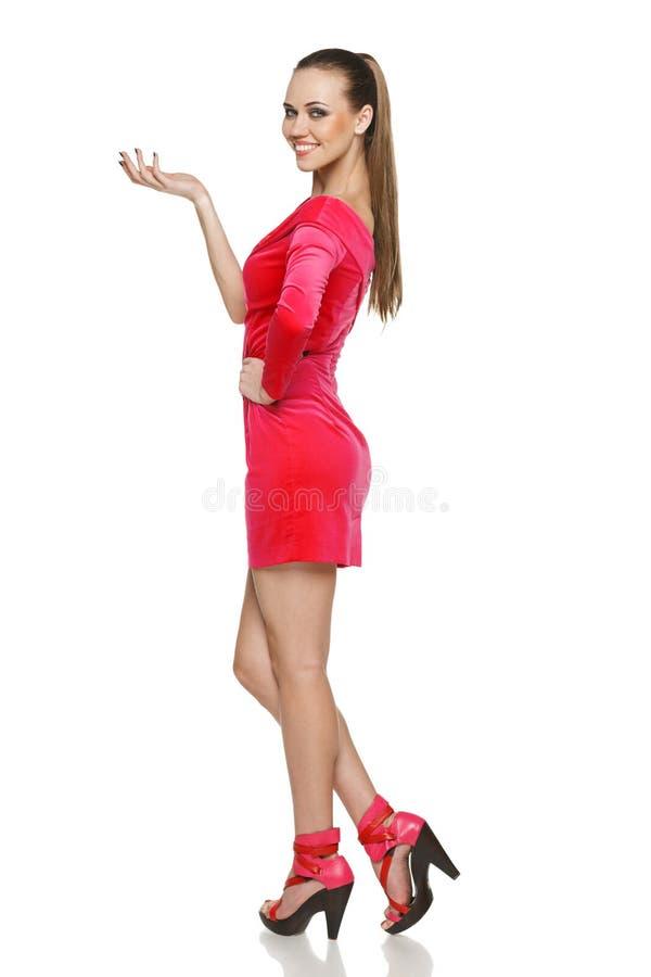 Кокетливая молодая женщина в розовом платье показывая пустой космос экземпляра стоковые фото