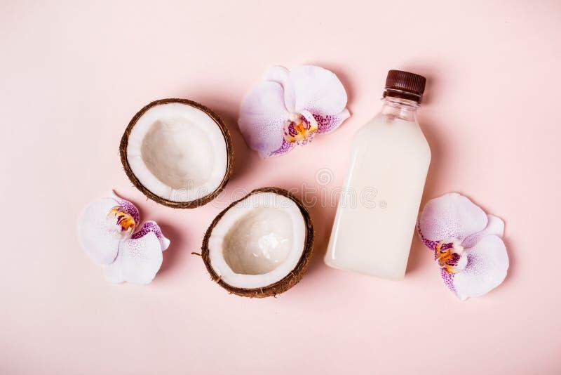 Кокосовое масло и половины свежего кокоса на розовой предпосылке Концепция курорта ухода за волосами стоковые фото