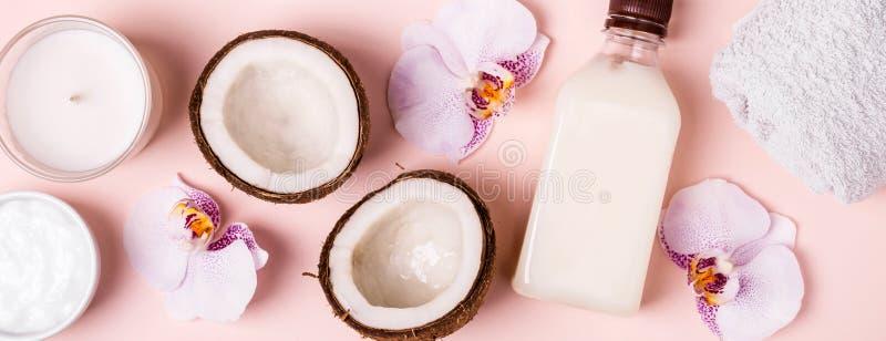 Кокосовое масло и половины свежего кокоса на розовой предпосылке Концепция курорта ухода за волосами стоковое фото