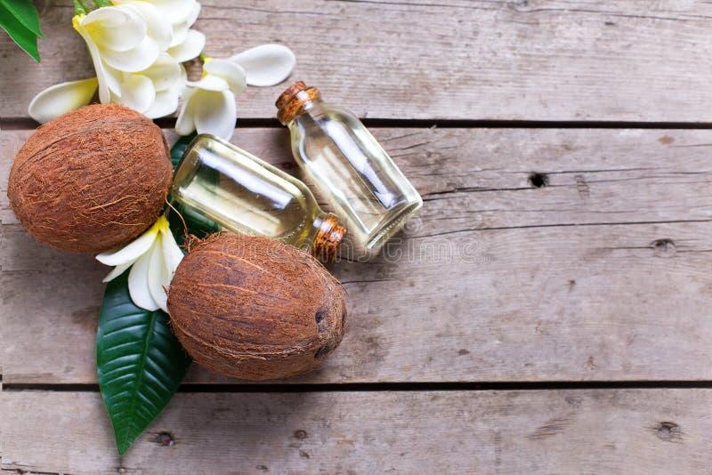 Кокосы и кокосовое масло на винтажной деревянной предпосылке стоковая фотография rf