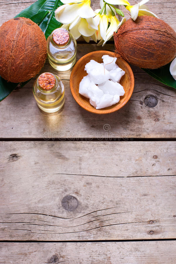 Кокосы и кокосовое масло на винтажной деревянной предпосылке стоковые фотографии rf