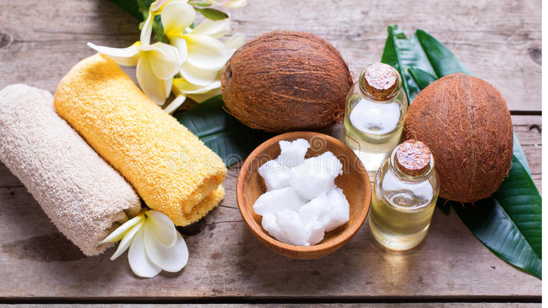 Кокосы, кокосовое масло и полотенца на винтажной деревянной предпосылке стоковая фотография