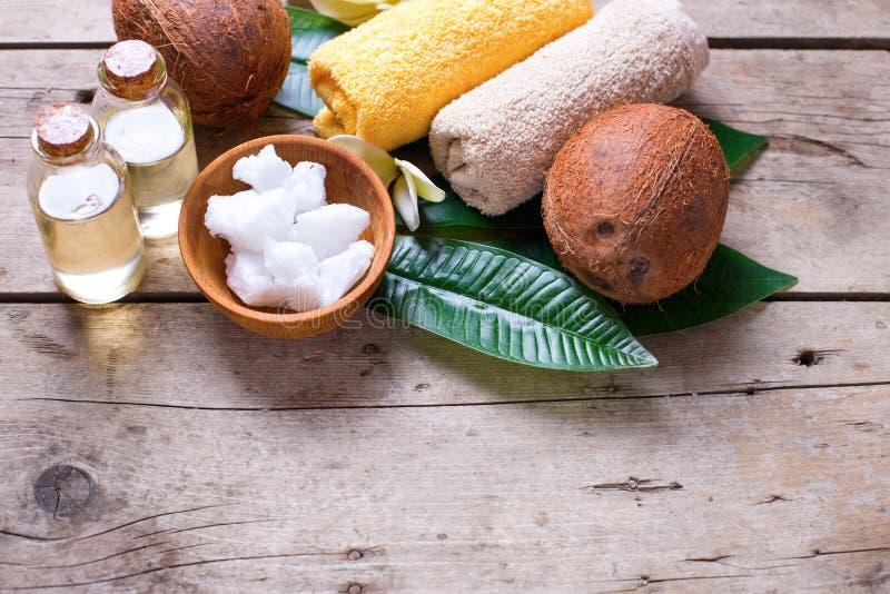 Кокосы, кокосовое масло и полотенца на винтажной деревянной предпосылке стоковые фото