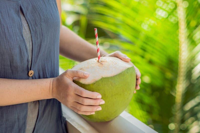 Кокос в красивых женских руках на зеленой предпосылке Преимущества концепции воды кокоса стоковая фотография