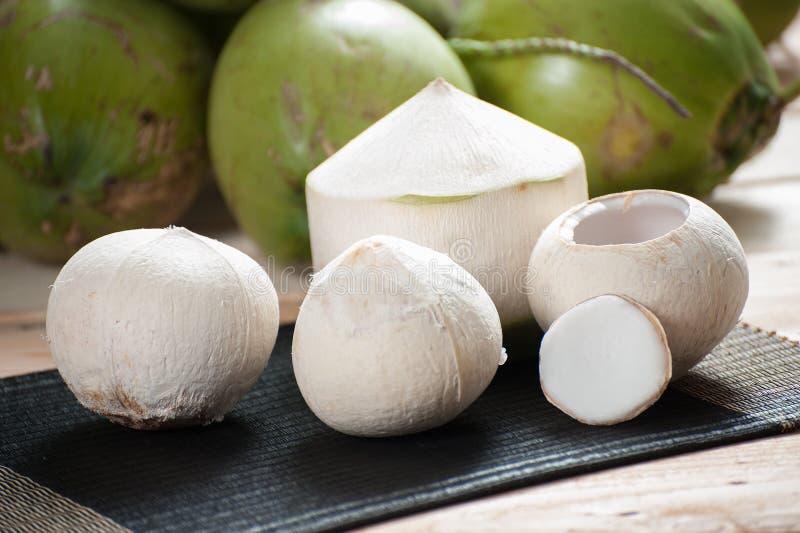 Кокос шелушения на циновке с зеленой предпосылкой кокоса стоковые фото