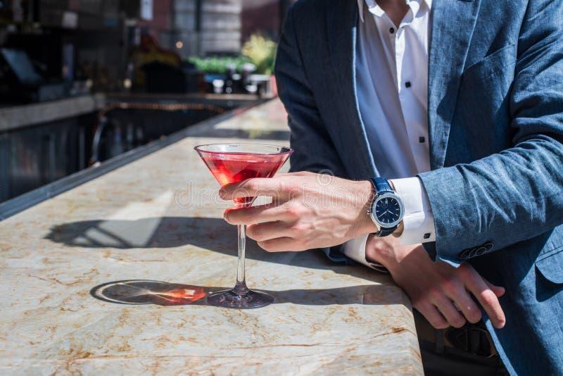 Коктеили элегантного человека выпивая на счетчике и ждать бара на сегодняшний день девушку стоковая фотография