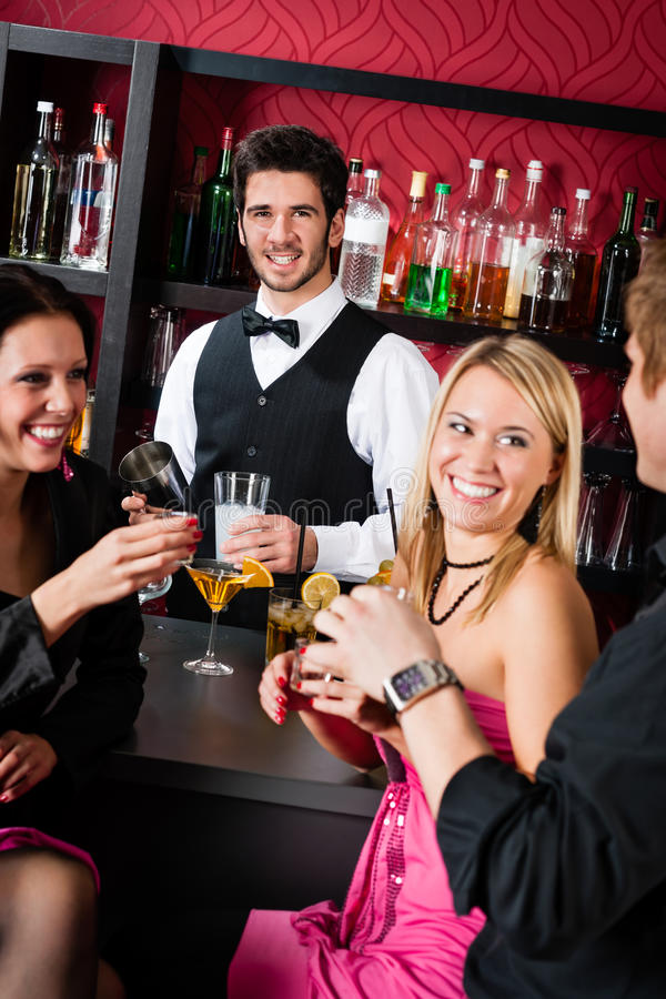 коктеилы barman штанги выпивая друзей подготовляют стоковое изображение