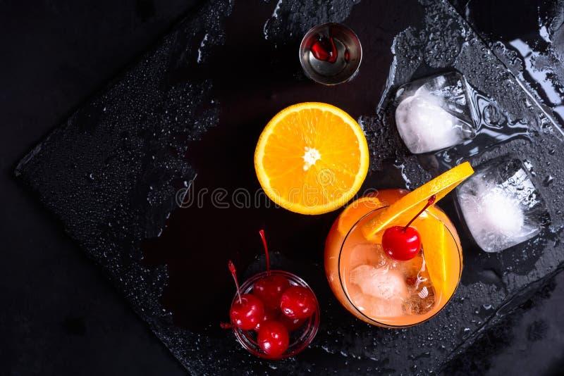 Коктеиль восхода солнца текила, апельсин, кубы льда, вишни maraschino и джиггер на влажном черном подносе шифера Комплект коктеил стоковое изображение rf