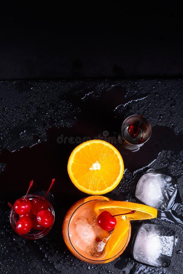 Коктеиль восхода солнца текила, апельсин, кубы льда, вишни maraschino и джиггер на влажном черном подносе шифера Комплект коктеил стоковые изображения rf