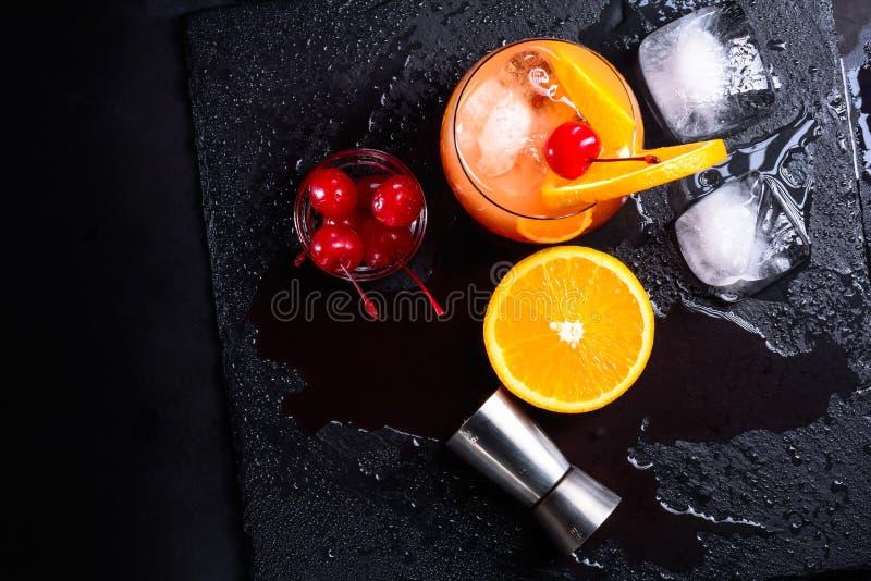 Коктеиль восхода солнца текила, апельсин, кубы льда, вишни maraschino и джиггер на влажном черном подносе шифера Комплект коктеил стоковое фото rf