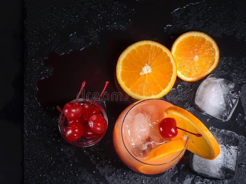 Коктеиль восхода солнца текила, апельсин, кубы льда и вишни maraschino на влажном черном подносе шифера Взгляд сверху стоковые фотографии rf