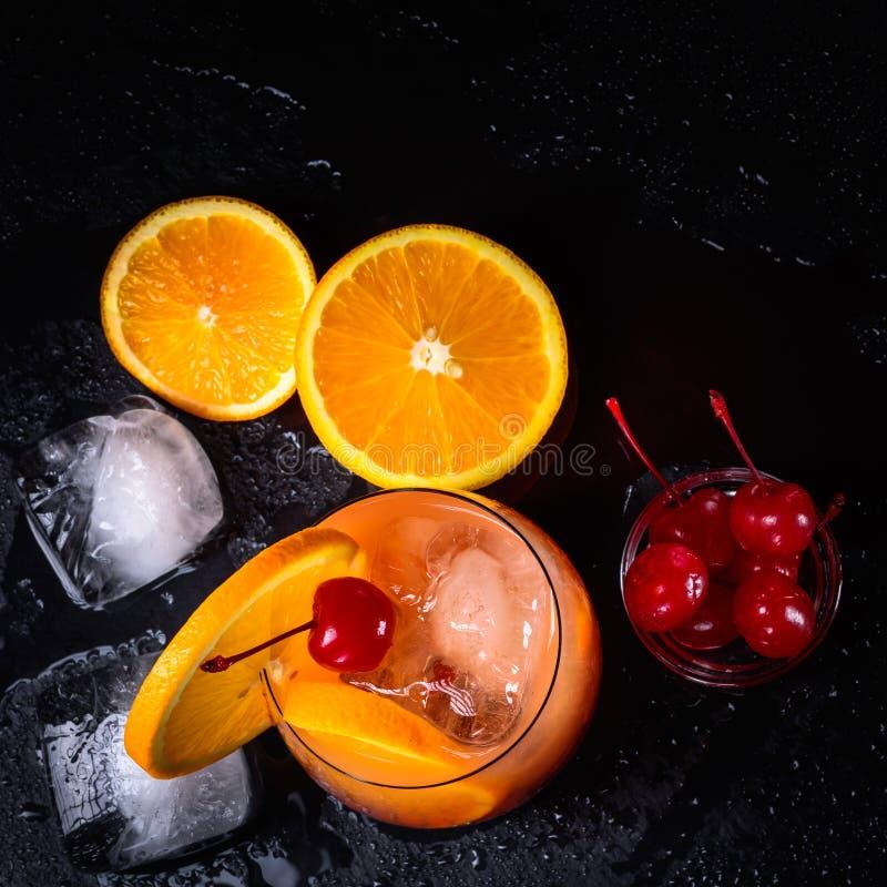 Коктеиль восхода солнца текила, апельсин, кубы льда и вишни maraschino на влажном черном подносе шифера Взгляд сверху с космосом  стоковые фото