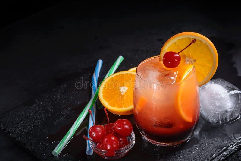Коктеиль восхода солнца текила, апельсин, куб льда, вишни maraschino, соломы на влажном черном подносе шифера с космосом экземпля стоковое фото