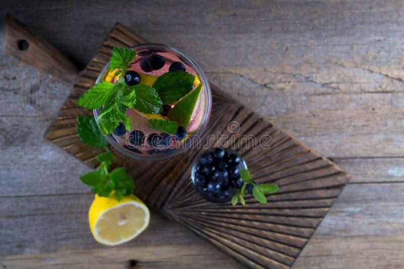 Коктеиль голубики - Mojito с свежими лимоном, известкой, льдом и мятой ягоды на старом деревянном взгляд сверху предпосылки, стоковые изображения