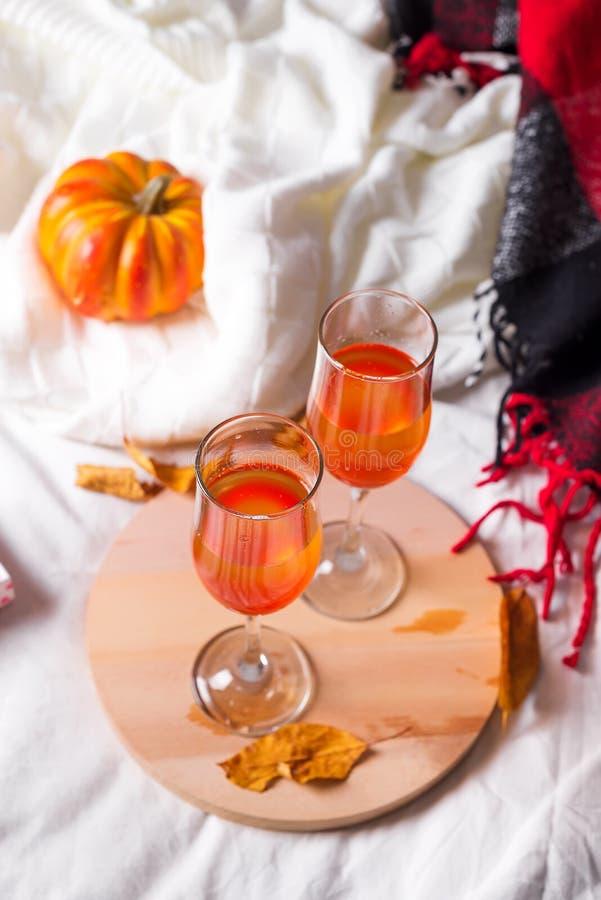 Коктеиль хеллоуина, питье тыквы оранжевое с специями на деревянной доске в белой кровати стоковая фотография rf