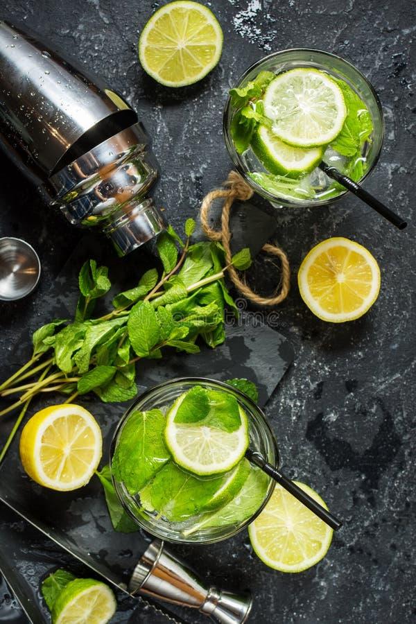 Коктеиль Mojito с известкой и мятой в стекле highball на каменной таблице Питье делая инструменты и ингридиенты для коктеиля стоковая фотография rf
