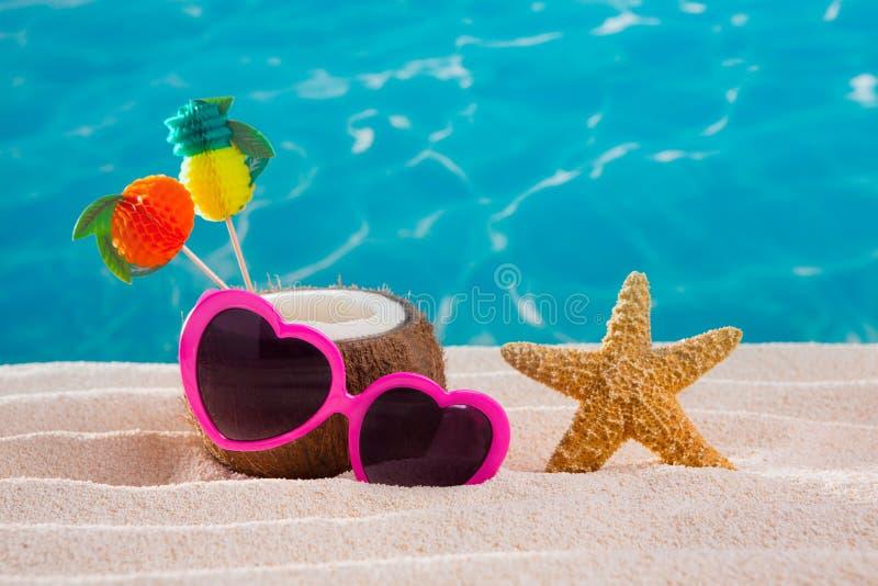 Коктеил кокоса на тропических солнечных очках сердца пляжа песка стоковое фото rf