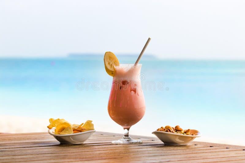 Коктейль с плодами, кусок банана на верхней части и солома на деревянном столе над предпосылкой пляжа в Мальдивах стоковая фотография
