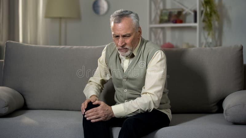 Колено удерживания старика, страдая совместная боль, старший артрит, остеопороз стоковое фото