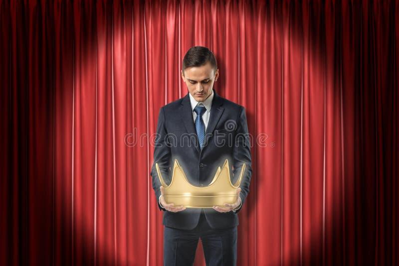 Колен-глубокий вид спереди бизнесмена смотря вниз на кроне золота которую он держит в руках, на красном занавесе этапа стоковая фотография rf
