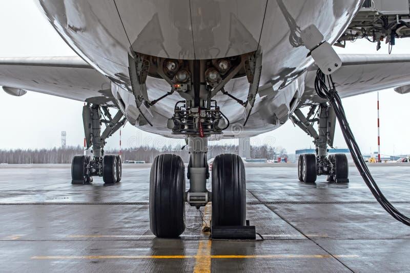 Колеса посадочного устройства и воздушных судн припарковали на авиапорте, с основным электропитанием стоковые фотографии rf